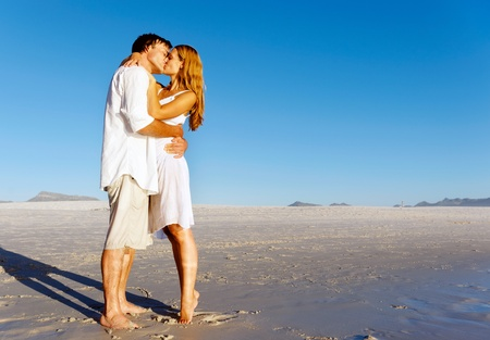 tiptoe: Couple in love stand on the beach in summer and share a kiss at sunset alone and on honeymoon. Stock Photo