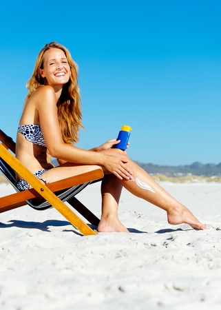 Beautiful young woman apllying sunblock to her legs while sitting on a beach in summer.