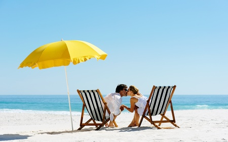 Beach summer couple kissing on island vacation holiday in the sun on their deck chairs under a yellow umbrella. Idyllic travel background.