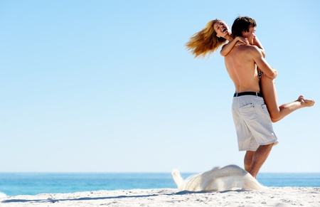 Happy couple playing on the beach, summer spin and hug embrace photo