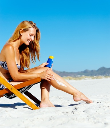 sunscreen: Beautiful young woman apllying sunblock to her legs while sitting on a beach in summer.