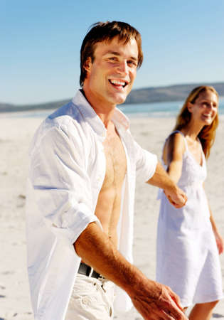 romantic honeymoon couple walk on the beach during a tropical summer holiday vacation. carefree stress free lifestyle concept. photo