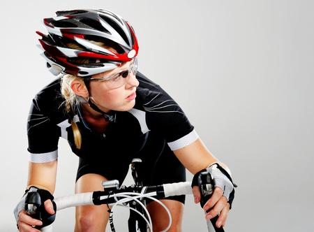 andando en bicicleta: Mujer, ciclismo todo terreno en su bicicleta y concentrarse en ganar la carrera ciclista. equipo de ciclo completo y la acci�n como un ciclista trenes reales para el ejercicio f�sico. aislado en gris.