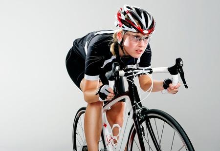 ciclista: Mujer, ciclismo todo terreno en su bicicleta y concentrarse en ganar la carrera ciclista. equipo de ciclo completo y la acci�n como un ciclista trenes reales para el ejercicio f�sico. aislado en gris.
