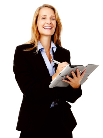 Businesswoman writing in her organizer diary while smiling and happy photo