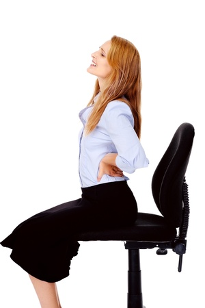 Young businesswoman suffers from back pain caused by her office chair Stock Photo