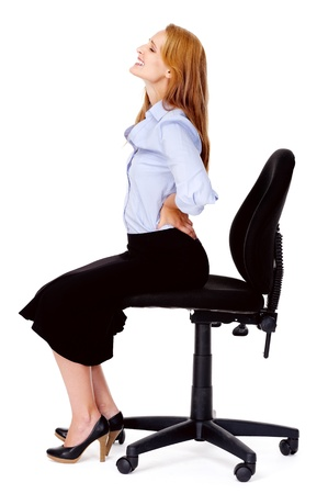 caused: Young businesswoman suffers from back pain caused by her office chair Stock Photo