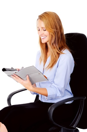 succesful: businesswoman writing in her organizer smiling and happy