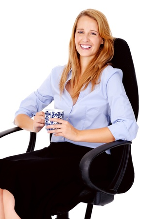 succesful: young business woman happy and smiling while holding a coffee mug and sitting in her office chair