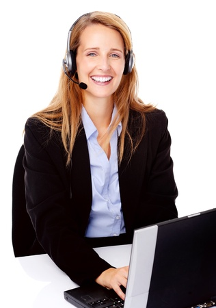 succesful: young attractive businesswoman working at her desk with a laptop and headset. happy and smiling Stock Photo