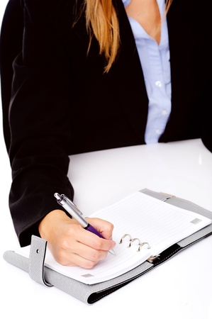 Business person writing in a daily organizer photo