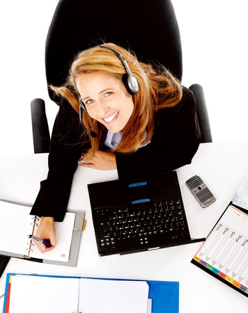 Business woman working at her desk, happy and smiling as she multitasks photo