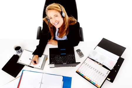 succesful: Business woman working at her desk, happy and smiling as she multitasks