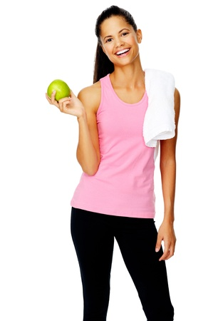 confident young sporty hispanic woman holds a fresh apple after a gym session promoting healthy eating and healthy lifestyle Stock Photo - 13183444