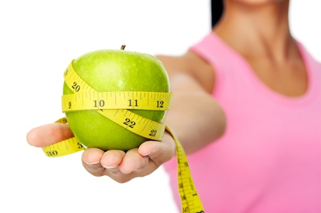 Healthy happy hispanic woman with apple and tape measure for diet and weight loss concept photo