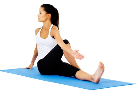 Part of a collection of yoga poses by a fit active hispanic woman; half spinal twist photo
