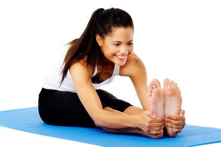 hamstrings: Athletic woman smiling while she stretches forward, Part of a collection of yoga poses by a fit active hispanic woman; sit-up pose Stock Photo