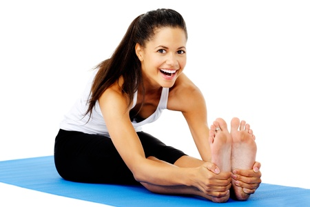 Athletic woman smiling while she stretches forward, Part of a collection of yoga poses by a fit active mixed race woman; sit-up pose. photo