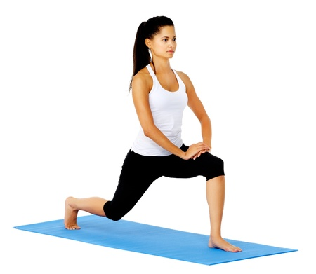 knees bent: Healthy latino woman stands on a yoga mat and stretches her hamstring muscles before a workout, isolates on white