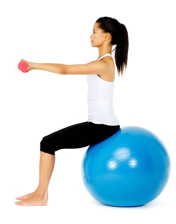 toning: Happy fit asian woman sitting on a gym ball while lifting dumbbells, isolated on white with pilates ball Stock Photo