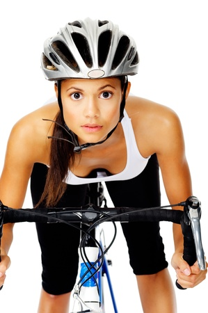 racing bicycle: Mixed race woman concentrates with a serious face, wearing a helmet on a bicycle Stock Photo