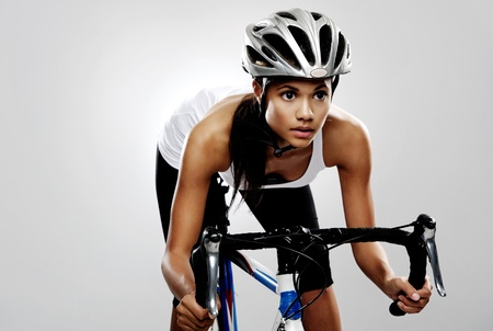 Cycling  race: Fit cyclist woman on road racing bicycle isolated in studio with dramatic lighting. Riding bike as if in a race. Stock Photo