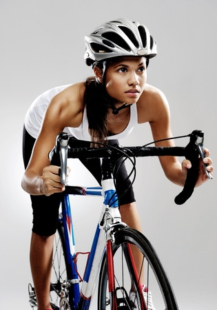 racing bike: Fit cyclist woman on road racing bicycle isolated in studio with dramatic lighting. Riding bike as if in a race. Stock Photo