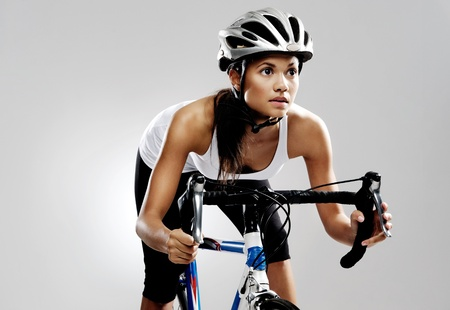 handlebars: Fit cyclist woman on road racing bicycle isolated in studio with dramatic lighting. Riding bike as if in a race. Stock Photo