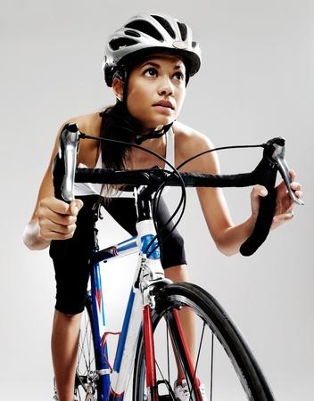 ciclismo: Ciclista de la mujer apta en la bicicleta de carreras de carretera aislado en estudio con iluminación espectacular. El montar en bicicleta como si en una carrera. Foto de archivo