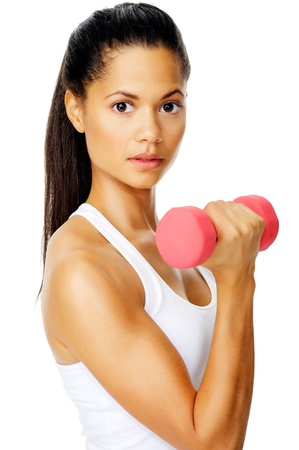 focuses: Beautiful latino woman focuses on her toning exercises with dumbbells in studio
