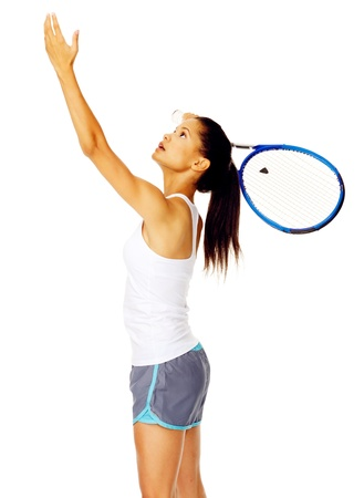 Healthy active mixed race female throws an imaginery tennis ball in the air and pretends to serve in studio photo