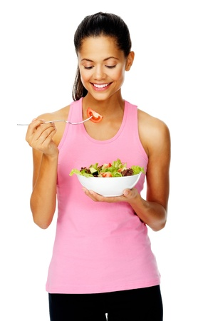 Portrait of a fit healthy hispanic woman eating a fresh salad isolated on white Stock Photo - 13303147