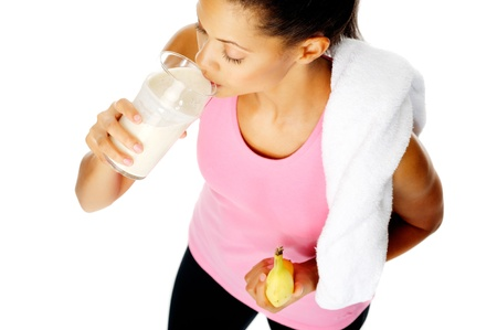 protien: portrait of a healthy hispanic woman with banana smoothie protien shake after gym session