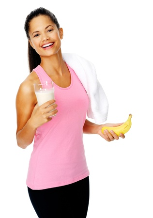 portrait of a healthy hispanic woman with banana smoothie protien shake after gym session photo