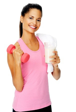 woman drinking milk: portrait of a beautiful hispanic girl with dumbbell and protien shake