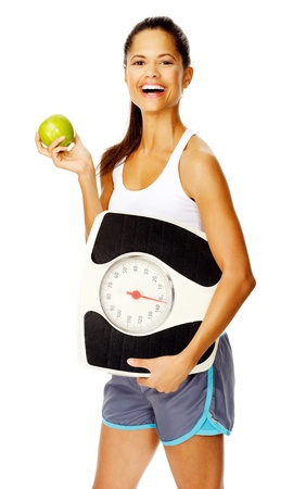 woman on scale: portrait of a slim fitness woman with apple and scale promoting healthy weightloss