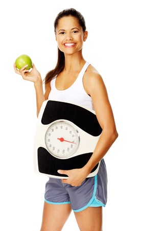 portrait of a slim fitness woman with apple and scale promoting healthy weightloss photo