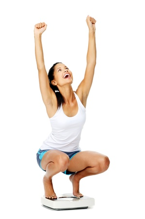 weight loss success: portrait of an excited hispanic woman on a scale who has lost weight and is fit and healthy