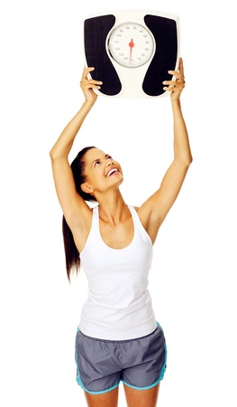 weight machine: portrait of a cheerful hispanic woman who is happy with her weight and holds scale above her head