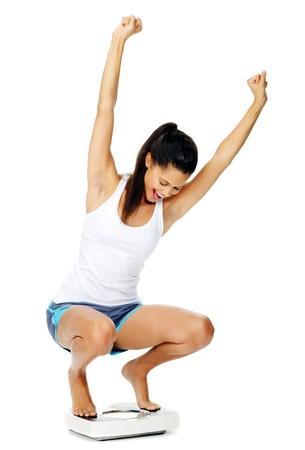 dieta sana: retrato de una mujer excitada hispano en una escala que ha perdido peso y est� en forma y saludable Foto de archivo