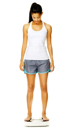 girl in sportswear: portrait of a woman full length with scale. unsure of whether to weigh herself or not.