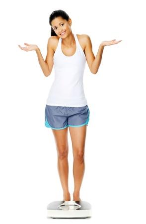 questionnement: portrait d'une femme pleine longueur avec une �chelle. pas s�r de savoir s'il faut se peser ou non.