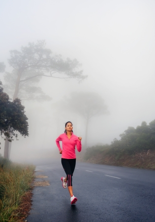 runner running outdoor fitness healthy lifestyle woman workout. female jogger on road run through misty forest early in the morning. photo