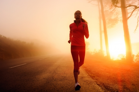 marathon running: Healthy running runner woman early morning sunrise workout on misty mountain road workout jog. sunflare through the mist gives atmospheric feel and depth to these fitness images