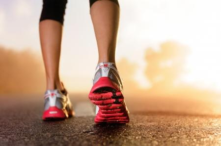 ジョグ: ランナーの足靴に道路のクローズ アップを実行しています。女性フィットネス日の出ジョグ ワークアウト ウェルネス コンセプト。