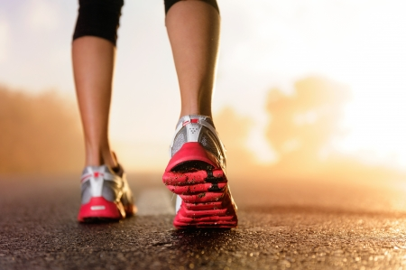 athletic activity: Runner feet running on road closeup on shoe. woman fitness sunrise jog workout welness concept.