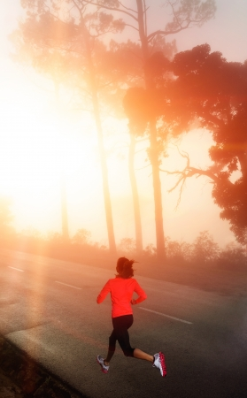 Healthy running runner woman early morning sunrise workout on misty mountain road workout jog. sunflare through the mist gives atmospheric feel and depth to these fitness images photo