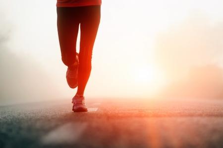 러너의 발을 신발에 도로 근접 촬영에서 실행. 여성 피트니스 일출 조그 운동 우미 개념.