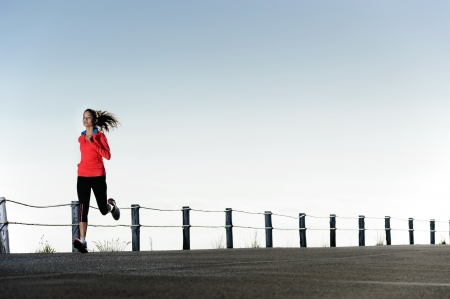 Runnign fitness training woman outdoors. Action healthy lifestyle image with copyspace photo