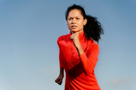 Portrait of an athlete running fitness woman with blue sky copyspace and red jacket. healthy athlete lifestyle. photo